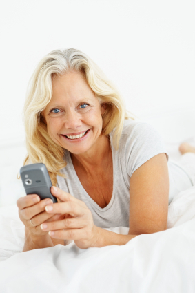 Senior woman with a mobile phone relaxing on bed